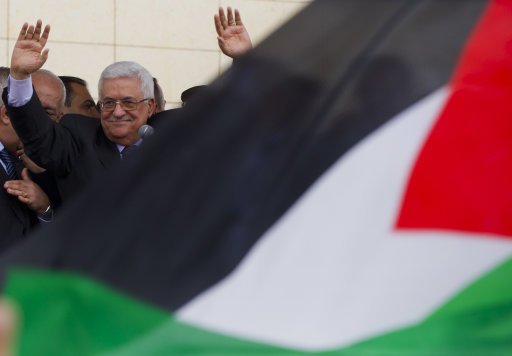 Palestinian President Mahmoud Abbas waves to supporters during his arrival at the government compound, in the West Bank city of Ramallah, Sunday, Sept. 25, 2011. Abbas has received a hero's welcome in the West Bank, triumphantly telling his people the