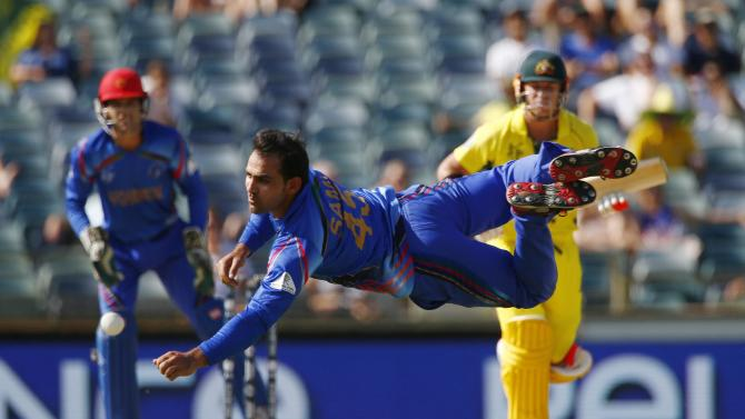 Afghanistan's bowler Shinwari dives for the ball off Australian batsman Warner, as wicketkeeper Zazi watches on, during their Cricket World Cup match in Perth