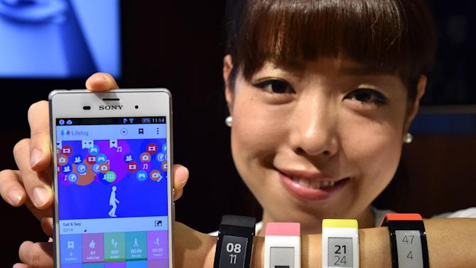 A Sony employee displays the new wristwatch styled smartwear 'SmartBand Talk' and the new smartphone 'Xperia Z3' at the company's headquarters in Tokyo, on September 9, 2014