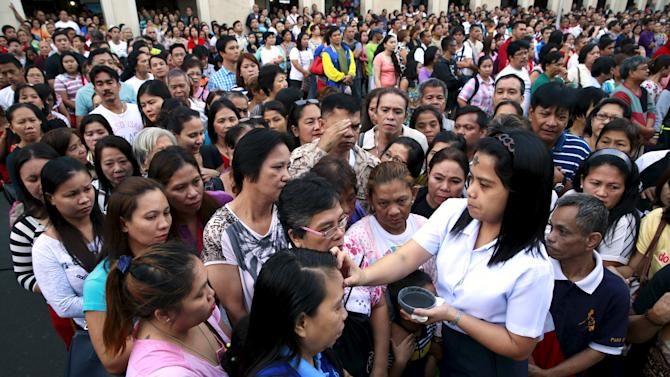 A Catholic nun marks a cross on the forehead of a devotee using ash during the observance of Ash Wednesday which marks the start of Lent at a Catholic church in Manila