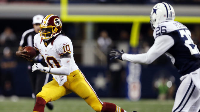 Washington Redskins quarterback Robert Griffin III (10) escapes from Dallas Cowboys strong safety Charlie Peprah (26) for a first down during the second half of an NFL football game, Thursday, Nov. 22, 2012, in Arlington, Texas. The Redskins won 38-31. (AP Photo/The Waco Tribune-Herald, Jose Yau)