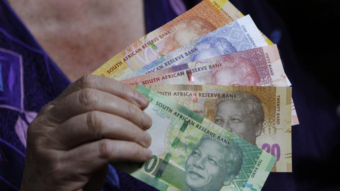 FILE -  In this photo taken Tuesday, Nov. 6, 2012, reserve bank governor Gill Marcus  displays bank notes bearing the image of former president Nelson Mandela, in Pretoria, South Africa. Across South Africa Mandela's face is a familiar sight, beaming from T-shirts, drink coasters  and new bank notes. But the sense of possibility that he embodied as a former prisoner of apartheid who became the country's frist black president is fading as a gulf between rich and poor widens and the gorvenrment has been tainted by corruption scandals.(AP Photo/Denis Farrell-file)