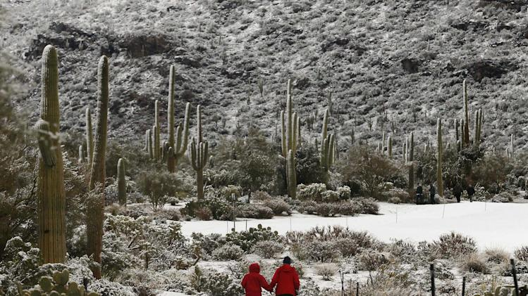 Tournament volunteers walk along the golf course after a snow storm suspended play for the day during the Match Play Championship golf tournament, Wednesday, Feb. 20, 2013, in Marana, Ariz. Play was suspended for the day. (AP Photo/Ross D. Franklin)