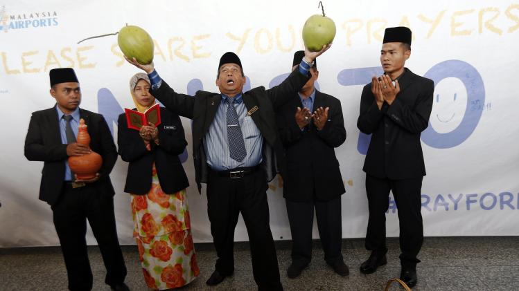 "Mat Zin, a local well-known ""bomoh"", holds two coconuts as he performs a ritual to help finding missing Malaysia Airlines MH370 at Kuala Lumpur International Airport"