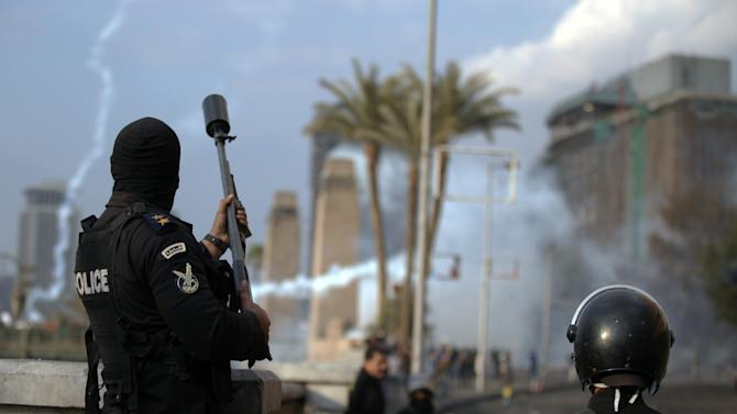 An Egyptian police officer fires tear gas at protesters during clashes near Tahrir Square, Cairo, Egypt, Tuesday, Jan. 29, 2013. Intense fighting for days around central Tahrir Square engulfed two landmark hotels and forced the U.S. Embassy to suspend public services on Tuesday. (AP Photo/Khalil Hamra)