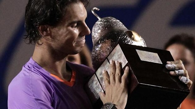 Rafael Nadal of Spain looks at his trophy after defeating compatriot David Ferrer during their men's singles final match at the Acapulco International tennis tournament in Acapulco March 2, 2013 (Retuers)