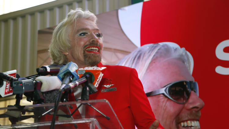 British entrepreneur Richard Branson speaks during a press conference while dressed up as an AirAsia flight attendant at a low cost carrier terminal in Malaysia, Sunday, May 12, 2013. Branson wore the costume during his flight from Australia to Malaysia after losing a bet with his friend AirAsia's Chief Executive Tony Fernandes on which of their 2010 Formula One racing car teams would finish ahead of the other. (AP Photo/Vincent Thian)