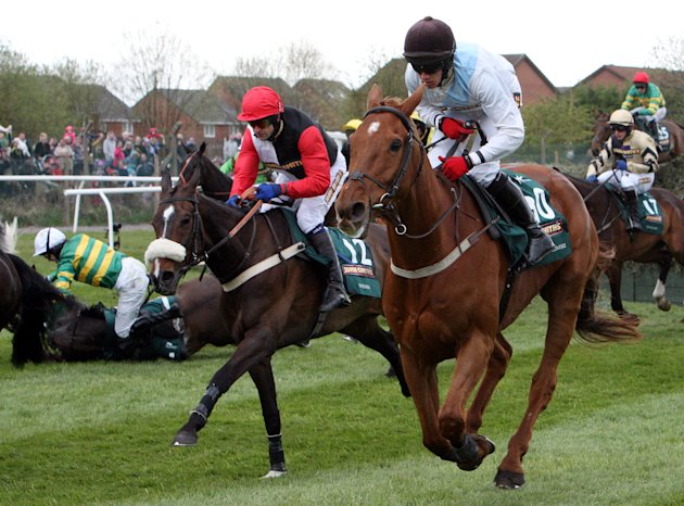 Synchronised, ridden by Tony McCoy, left, falls after jumping Becher&#39;s Brook the Grand National at Aintree Racecourse, Liverpool, England, Saturday April 14, 2012. Synchronised, who won the Cheltenham Gold Cup last month, suffered a fatal injury after falling early in the Aintree race, owner J.P. McManus announced. (AP Photo/Scott Heppell)
