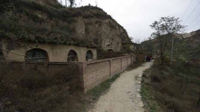 In this photo taken Thursday, Oct. 18, 2012, village officials and journalists gather near the cave dwellings where Chinese Vice President Xi Jinping used to live during his youth when he was sent to learn peasant virtues at Liangjiahe village  in northwestern China's Shaanxi province. Xi, 59 and the country's vice president is expected to take over as head of the ruling party in November, 2012, before becoming president in 2013 of an increasingly assertive China.The Liangjiahe years are among scant details known about Xi's life and personality partly because he himself chronicled them as a key formative experience.  (AP Photo/Ng Han Guan)