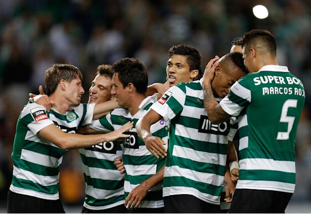 Sporting's Montero, from Colombia, center, sticks his tongue out while celebrating after scoring his second goal against Setubal  during their Portuguese league soccer match Saturday, Oct. 5 2013, at