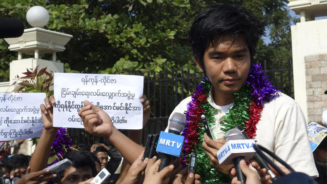"""Released political prisoner Yan Naing Tun, listens to a reporter's question outside Insein Prison, in Yangon, Myanmar, Tuesday, Dec.31, 2013. Myanmar freed five prisoners Tuesday and more are expected to be released next week as part of pledge by the country's president to free all political prisoners by the end of 2013. President Thein Sein granted a pardon Monday to those convicted of or charged with a variety of political offenses, such as unlawful association, high treason, contempt of government and violations of the peaceful assembly law. The placard in the background reads: """"We warmly welcome Ko Yan Naing Tun and Ko Aung Min Naing from the group that staged the march to Laiza."""" (AP Photo/Khin Maung Win)"""