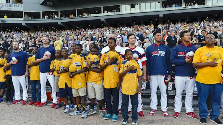 Members of the Jackie Robinson West Little League team sing the national anthem with the Chicago White Sox before the second game of the White Sox's baseball doubleheader against the Detroit Tigers in Chicago on Saturday, Aug. 30, 2014. (AP Photo/Matt Marton)