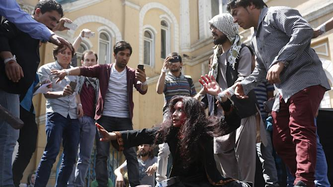 Afghan artists perform a re-enactment of the lynching of Farkhunda, a 27-year old woman, to protest against her killing in Kabul