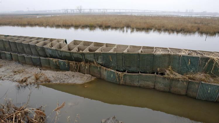 In this Dec. 8, 2012 photo, the battered and emptied Richard P. Kane Wetland Mitigation Bank, a long barrier wall made of large baskets filled with sand and dirt, runs through the Meadowlands in Moonachie, N.J. The barrier was built primarily to control the movement of tidewaters in and out of the wetlands area and not for flood protection. But since the tidal surge from Superstorm Sandy washed over it and damaged more than 2,000 homes and other buildings, attention has turned to what can be done to prevent similar river flooding in future storms. Unfortunately, however, no one seems to own the problem. (AP Photo/Mel Evans)