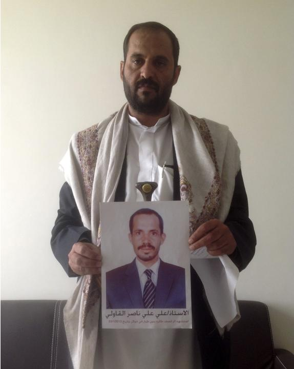 Qawli poses with a photograph of his brother who was killed in a January 2013 U.S. drone strike on the Yemeni village of Khawlan.