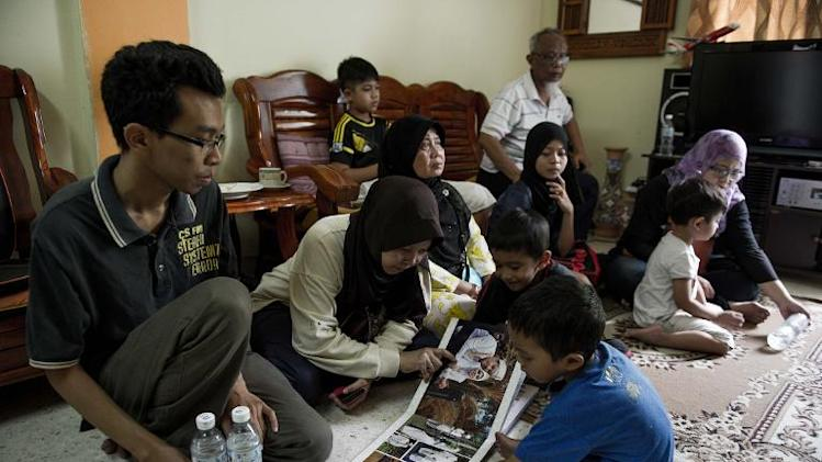 Family of 34-year-old Norliakmar Hamid, a passenger on the missing Malaysia Airlines plane, gather at their home