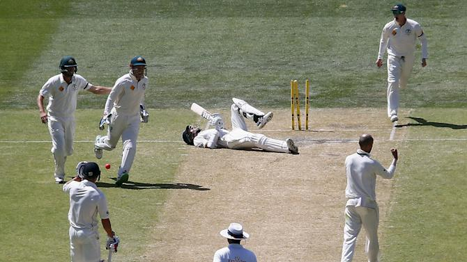 New Zealand's Mitchell Santner lies on the pitch after being stumped by Australia's wicketkeeper Peter Nevill for 45 runs during the third day of the third cricket test match at the Adelaide Oval, in South Australia