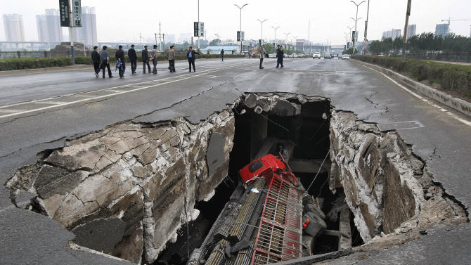 A truck is seen in a hole after part of the structure of a bridge collapsed in Changchun