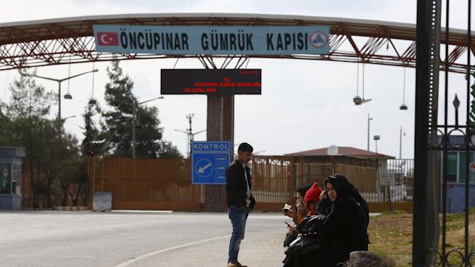Syrians wait at Turkey's Oncupinar border crossing on the Turkish-Syrian border in the southeastern city of Kilis