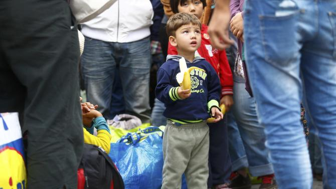A young migrant child eats a banana after arriving at a railway station in Vienna