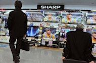Customers look at Sharp televisions in a Tokyo store. The company will slash 5,000 jobs by March, reports said Thursday, its first cuts since 1950 as it is hit by a prolonged slump in its key television and liquid crystal display sectors