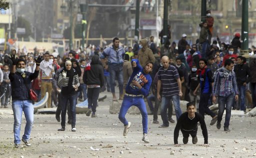 Demonstrators against Egypt's President Mursi throw stones at riot police during clashes in Cairo