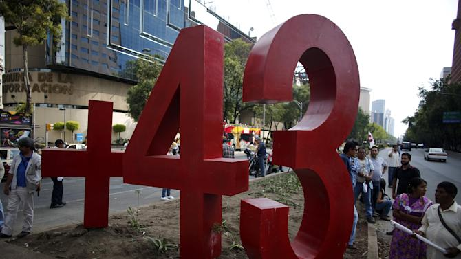 People stand next to a monument of the number 43 during a protest to mark the seven months of the Ayotzinapa students' disappearance in Mexico City