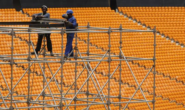 Workers climb scaffolding while constructing a stage ahead of Mandela's national memorial service at FNB Stadium in Johannesburg