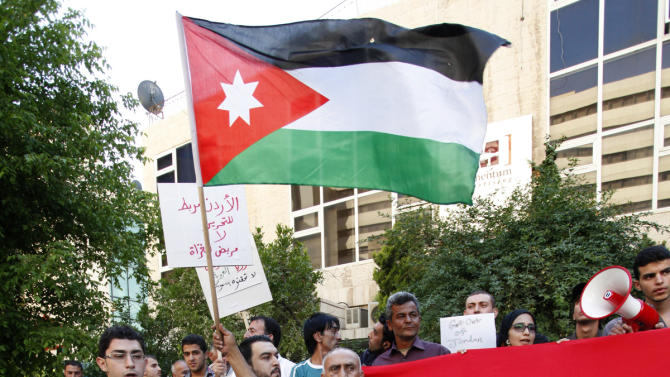"""Protesters wave a Jordanian national flag as they stand on the Syrian revolution flag outside of the the Friends of Syria conference, in Amman, Jordan, Wednesday, May 22, 2013.  As U.S. Secretary of State John Kerry and his counterparts arrived at the meeting venue in Amman, about 250 pro-Assad demonstrators blocked the main entrance. The protesters, a mix of Jordanians and Syrians, chanted """"Death to America,"""" and, """"Go home, Kerry we don't want you here.""""(AP Photo/Mohammad Hannon)"""