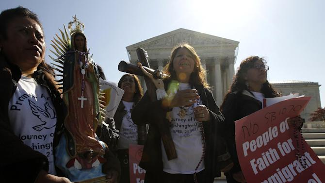 """Opponents of Arizona's """"show me your papers"""" immigration law rally in front of the Supreme Court in Washington, Wednesday, April 25, 2012, as the court held a hearing . (AP Photo/Charles Dharapak)"""
