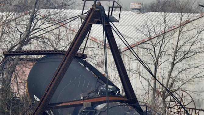 Officials stand by derailed freight train tank cars in Paulsboro, N.J., Friday, Nov. 30, 2012. People in three southern New Jersey towns were told Friday to stay inside after a freight train derailed and several tanker cars carrying hazardous materials toppled from a bridge and into a creek. At least one tanker car may contain vinyl chloride, Gloucester County Emergency Management director J. Thomas Butts told WPVI-TV. (AP Photo/Mel Evans)