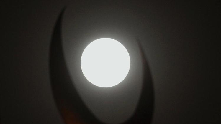 A perigee moon, also known as a supermoon, looks through a crescent of the dome of the grand Faisal mosque in Islamabad, Pakistan, Saturday, July 12, 2014. (AP Photo/Anjum Naveed)
