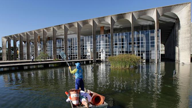 A worker collects objects in the reflection pool found after protesters tried to enter Itamaraty Palace, the foreign ministry's headquarters, in Brasilia, the capital of Brazil, Friday, June 21, 2013. Police and protesters fought in the streets into the early hours Friday in the biggest demonstrations yet against a government viewed as corrupt at all levels and unresponsive to its people. (AP Photo/Eraldo Peres)