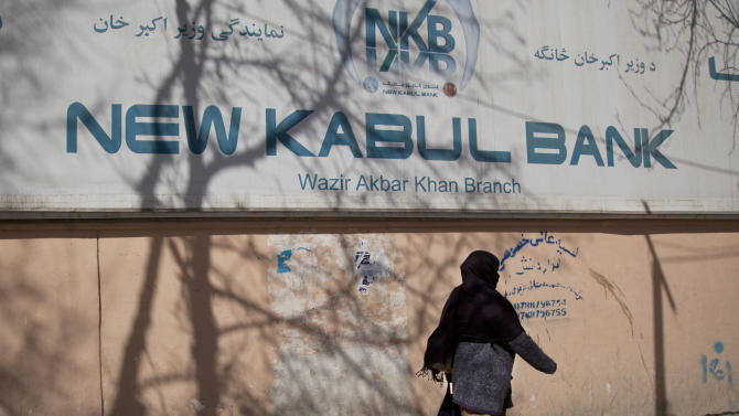 An Afghan woman passes by a sign of the New Kabul Bank in the center of Kabul, Afghanistan, Tuesday, March 5, 2013. An Afghan tribunal convicted two top executives of the Kabul Bank, renamed the New Kabul Bank after the scandal broke, and sentenced them to five-year prison terms on Tuesday for their role in a massive corruption scandal that led to the collapse of Afghanistan's largest bank and threatened the country's fragile economy. The bank's former chairman Sherkhan Farnood and former chief executive officer Khalilullah Ferozi were found guilty of theft of $278 million and $530 million, respectively. Farnood and Ferozi have also been ordered to pay back these funds. (AP Photo/Anja Niedringhaus)