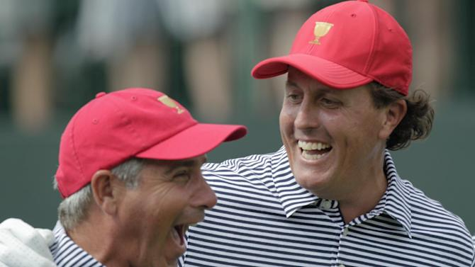 United States' Phil Mickelson, right, and team captain Fred Couples laugh together while walking down the first tee during a foursome match against the International team at the Presidents Cup golf tournament at Muirfield Village Golf Club Friday, Oct. 4, 2013, in Dublin, Ohio. (AP Photo/Jay LaPrete)