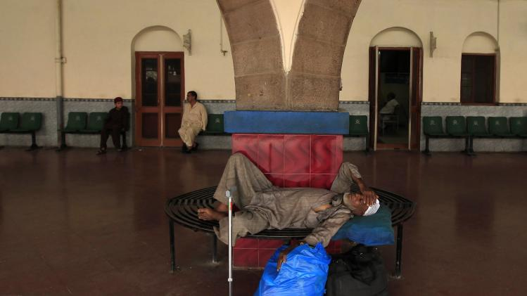 A man rests on a bench with his belongings as he waits for a train back home in Rawalpindi