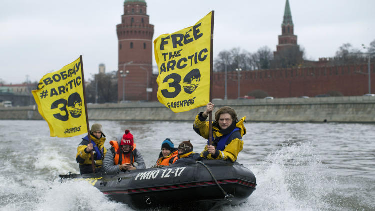 Greenpeace International activists on an inflatable boat pass by The Kremlin while making their way through the Moskva River as they protest against Russia's detention of members of the environmental group in Moscow, Russia, Wednesday, Nov. 6, 2013. Russia's main investigative agency said Wednesday, Oct. 23, 2013 that it has dropped piracy charges against jailed Greenpeace activists and charged them instead with hooliganism, which could still mean years in prison. (AP Photo/Alexander Zemlianichenko)