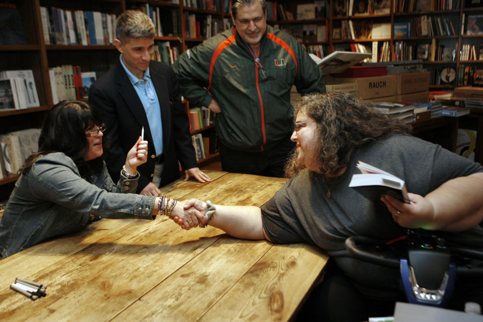 "Author E L James, left, greets Lynda Pyndall during a book signing for her new erotic fiction ""Fifty Shades of Grey"" in Coral Gables, Fla., Sunday, April 29, 2012. Publicist Russell Perreault watches at rear. (AP Photo/Jeffrey M. Boan)"