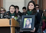 Jillian Soto, sister of Sandy Hook Elementary School shooting victim Victoria Soto, left, speaks as her cousin Heather Cronk, right, holding photograph of Soto, listens, during a rally at the Capitol in Hartford, Conn., Thursday, Feb. 14, 2013. Thousands of people turned out to call on lawmakers to toughen gun laws in light of the December elementary school shooting in Newtown that left 26 students and educators dead. (AP Photo/Jessica Hill)