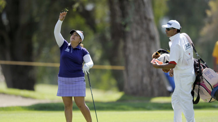 Lizette Salas, left, throws pieces of grass into the air to test the wind on the ninth hole during the third round of the LPGA Kraft Nabisco Championship golf tournament in Rancho Mirage, Calif., Saturday, April 6, 2013. At right is caddie, Greg Puga. (AP Photo/Rodrigo Pena)