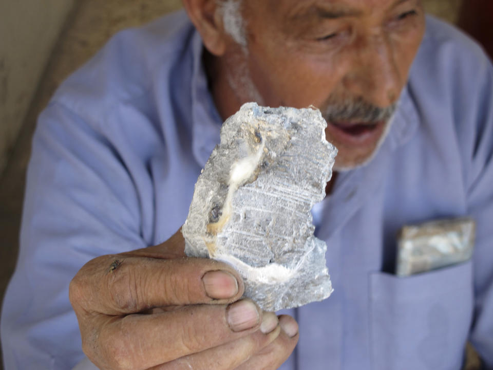 Syrian Mahmoud Jikar holds a piece of shrapnel he found in his house, which was destroyed in a Syrian government bombing last week that killed more than 40 people in Azaz, Syria, on Monday, Aug. 20, 2012. (AP Photo/Ben Hubbard)