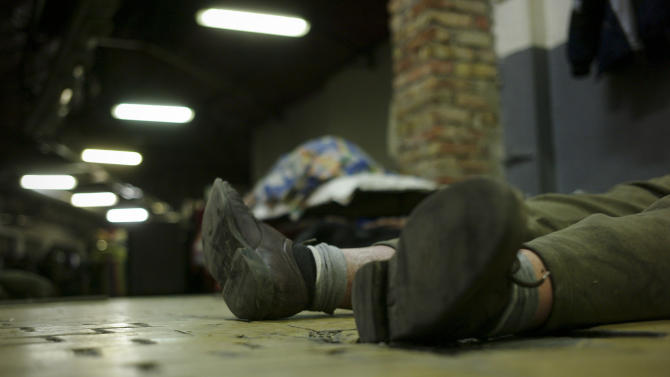 In this photo taken early morning Friday, Jan. 11, 2013, a homeless man sleeps on the floor in a shelter called 'The Heated Street' in Budapest, Hungary. Hungary considers constitutional change to allow authorities to force homeless off the streets. (AP Photo/Bela Szandelszky)