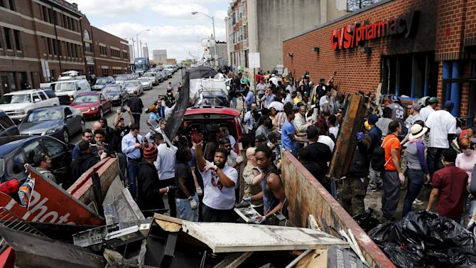Members of community work to clean up recently looted and burned CVS store in Baltimore