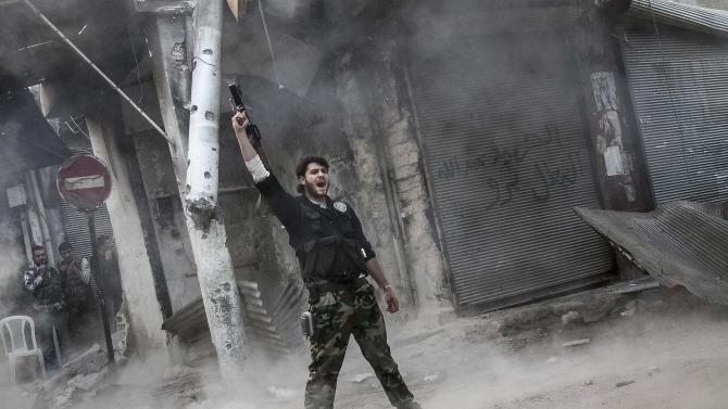 In this Sunday, Nov. 04, 2012 photo, a rebel fighter claims for victory after he fires a shoulder-fired missile toward a building where Syrian troops loyal to President Bashar Assad are hiding while they attempt to gain terrain against the rebels during heavy clashes in the Jedida district of Aleppo, Syria. The uprising against Assad started with peaceful demonstrations in March last year, but has since morphed into a bloody civil war. Activists say more than 36,000 people have been killed in 19 months of fighting. (AP Photo/Narciso Contreras)
