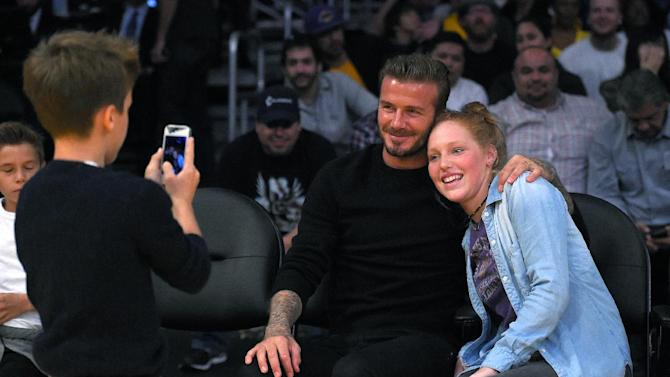 Retired soccer soccer star David Beckham, center, poses for a picture with fan Kim Friedman, 14, as Beckham's son Cruz takes it during the first half of a preseason NBA basketball game between the Los Angeles Lakers and the Utah Jazz, Sunday, Oct. 19, 2014, in Los Angeles