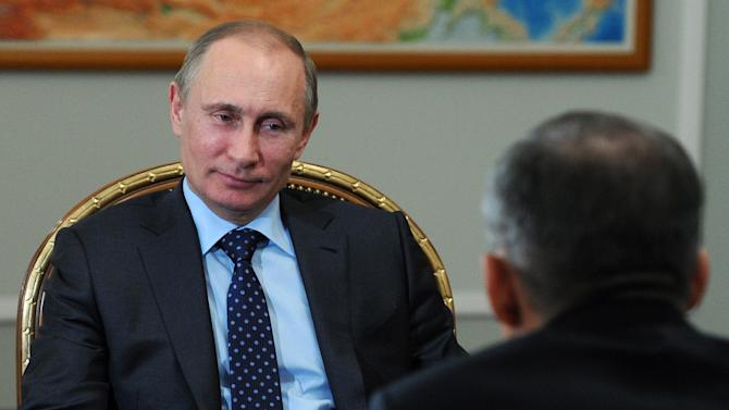 Russian President Vladimir Putin, left, speaks to Tatarstan regional leader Rustam Minnikhanov, back to camera, during a meeting at the Novo-Ogaryovo residence outside Moscow, Russia, Tuesday, April 1, 2014. Minnikhanov, who visited Crimea to attend a congress of Crimean Tatars, discussed their demands with Putin. (AP Photo/RIA-Novosti, Mikhail Klimentyev, Presidential Press Service)