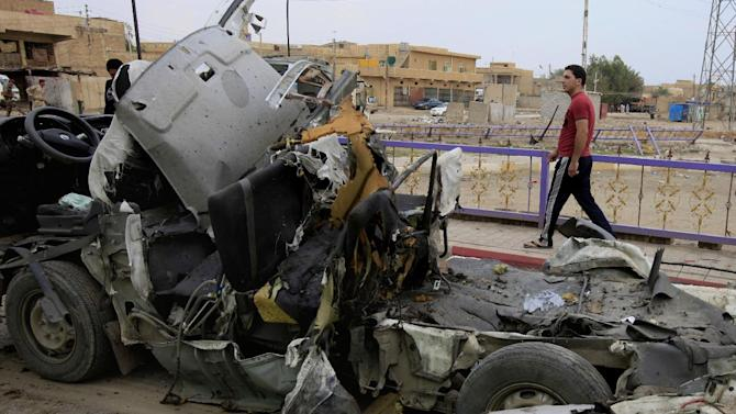 A man inspects the scene of a car bomb attack in the Husseiniyah suburb of northeastern Baghdad, Iraq, Monday, May 6, 2013. Two car bombs blew up in a Baghdad suburb, killing and wounding dozens of people, police said, in the deadlier of two attacks on Monday in the Iraqi capital. (AP Photo/ Karim Kadim)