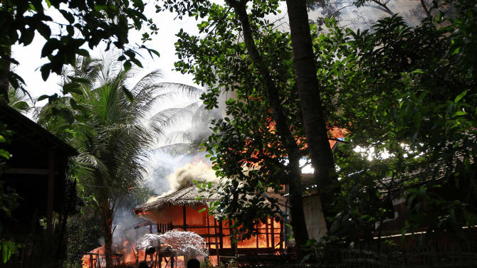 People look on a house engulfed in flames in Sittwe, Myanmar, Monday, June 11, 2012. With fearful residents cowering indoors, security forces patrolling a tense town in western Myanmar collected bodies Monday from the debris of homes burned down over the weekend in some of the country's deadliest sectarian bloodshed in years. The Buddhist-Muslim violence, which has left at least seven people dead and hundreds of homes torched since Friday, poses one the biggest tests yet for Myanmar's new government as it struggles to reform the nation after generations of military rule. (AP Photo/Kihn Maung Win)