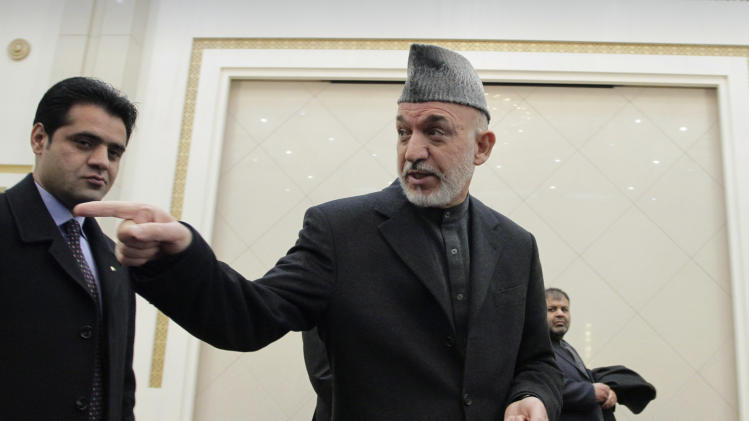 Afghan President Hamid Karzai gestures toward a journalist, not pictured, at the end of his press conference at the presidential palace in Kabul, Afghanistan, Sunday, Feb. 26, 2012. Afghanistan's president renewed his calls for calm Sunday in a televised address to the nation after the burning of Qurans at a U.S. base sparked five days of deadly protests and prompted the international military coalition to pull its advisers from Afghan ministries out of fear that they would become the next targets. (AP Photo/Musadeq Sadeq)