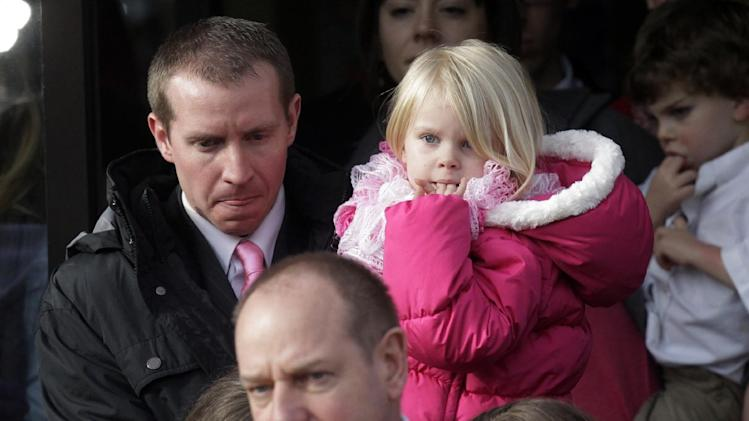 Robbie Parker, left, carries his daughter, Madeline, 4,  following funeral services for his 6-year old daughter, Connecticut elementary shooting victim Emilie Parker, Saturday, Dec. 22, 2012, at The Church of Jesus Christ of Latter-day Saints, in Ogden, Utah. Emilie, whose family has Ogden roots, was one of the victims killed in a Dec. 14 mass shooting at Sandy Hook Elementary in Newtown, Conn. (AP Photo/Rick Bowmer)